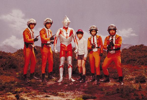 Ultraman entouré des membres de l'AIS et du jeune Hoshino Isamu qui avait obtenu l'autorisation de rejoindre l'équipe. CR :Tsuburaya Pro