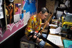 Au lendemain du Sanja Matsuri qui a vu déferler sur le quartier près de deux millions de personnes, Asakusa retrouve son rythme nonchalant. Le patron d'un snack-bar prend une leçon de shamisen
