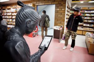 Tokyo, February 15 2012 - Japanese electronic books on display at Kinokuniya book shop in the Shinjuku area. A statue reading on the Sony reader.