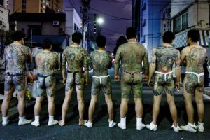 Tokyo, May 19 2013 - Yakuza members showing their tattoos on the street at the end of the last day of Sanja matsuri, in the Asakusa area.