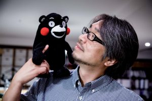 Tokyo, June 9 2014 - Portrait of Japanese author, screenwriter and radio personality Kundo KOYAMA at his office in the Toranomon area. Mr KOYAMA hold the mascot of Kumamoto prefecture, Kumamon. He was charged with promoting the prefecture when a new bullet train service linking Kumamoto with the commercial hub of Osaka was being launched. Mr Koyama then asked art director Manabu Mizuno to create a campaign logo, and threw in the cuddly Kumamon as a bonus.