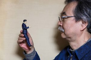 "Tokyo, November 9 2014 - Portrait of the manga artist Jiro Taniguchi in his atelier with a figurine of the main character of his series ""Kodoku no Gourmet"" (le gourmet solitaire in French))."