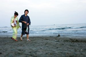 Japanese couple wearing yukata, on the beach of Kamakura before the fireworks