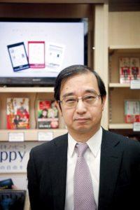 Tokyo, February 15 2012 - Portrait of Ushiguchi Junji, general manager of eCommerce division of Kinokuniya book stores, in front of the ebooks corner of the main Tokyo store in Shinjuku.